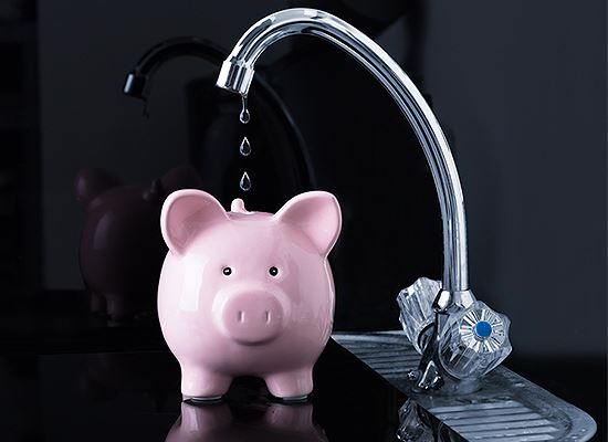 Dripping faucet with pink piggy bank